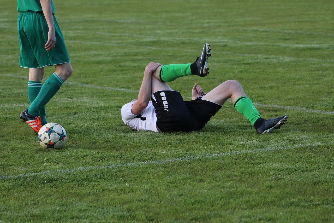 injured soccer player laying on the ground clutching knee
